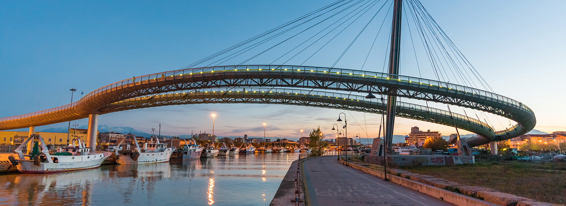 Pescara, Italy - 7 April 2017 - Urban landscape with the 'Ponte del Mare' monumental bridge at the dusk, in the canal and port of Pescara city, Abruzzo region